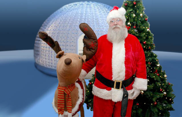 Santa in front of Magical Igloo in landscape